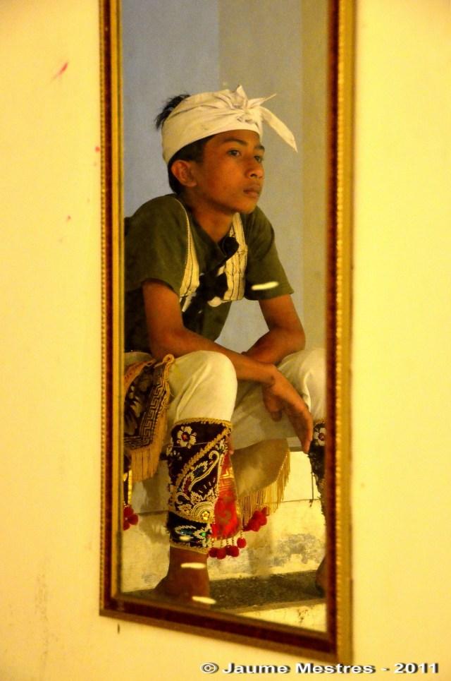 L'aleví de la família del mestre Anom Agung reflectit al mirall. A mig abillar, abans d'interpretar la dansa amb màscara Jauk Keras.
