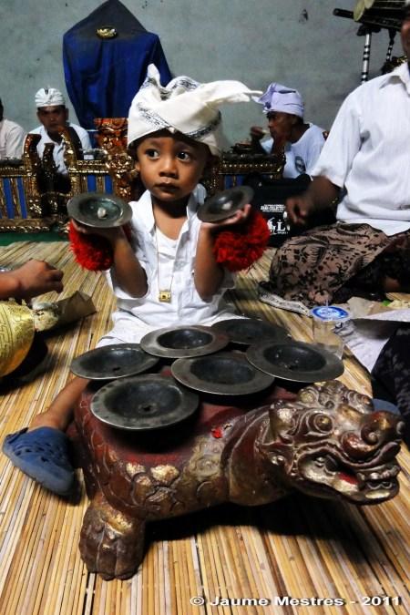 El fill d'un músic de gamelan practicant amb els platerets durant una nit de cerimònia al temple Pura Penataran, de Pengosekan.