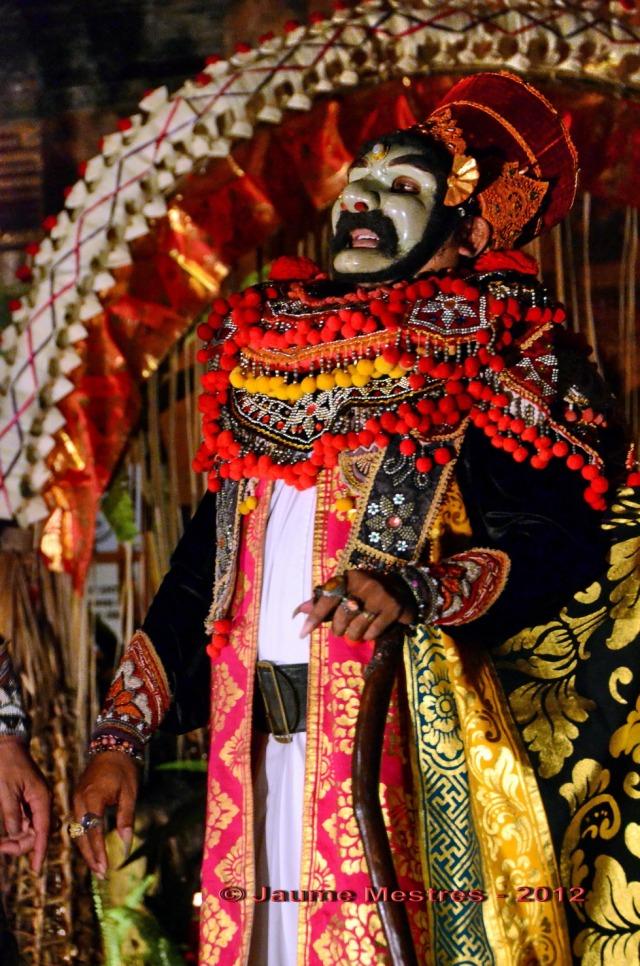 Dansa amb màscara, o topeng, al pati de palau durant la primera nit de les celebracions del funeral de Pak Cokorda Putra Dharma Yudha, membre de la família reial d'Ubud, traspassat el dia 7 de juliol. El seu cos serà incinerat demà passat, el dia 28. En una cremació que sens dubte serà multitudinària.